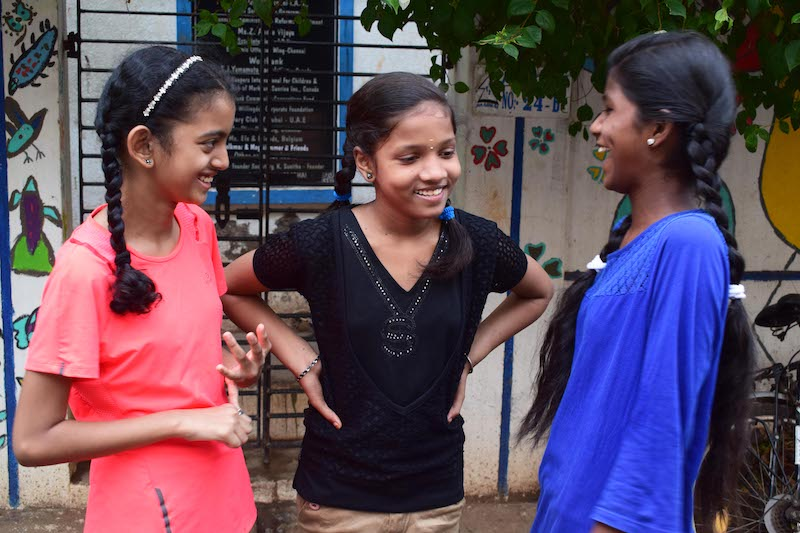 Technovation Girls 2019 Team Social Relay won first place junior division at World Pitch – the three young girls who are part of social relay stand in a semi-circle laughing and talking