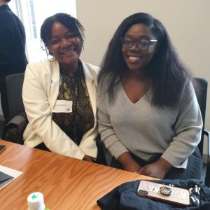 Technovation Girls Uber Job Shadow Day: Two young Black women are seated at a conference table, smiling